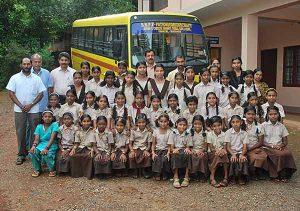Die Mädchen des Heims für Adivasi Kinder vor ihrem Schulbus